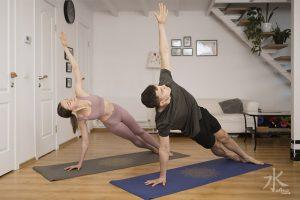 Pareja practicando yoga en el salón