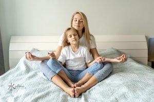 Madre y su hija meditan en la cama