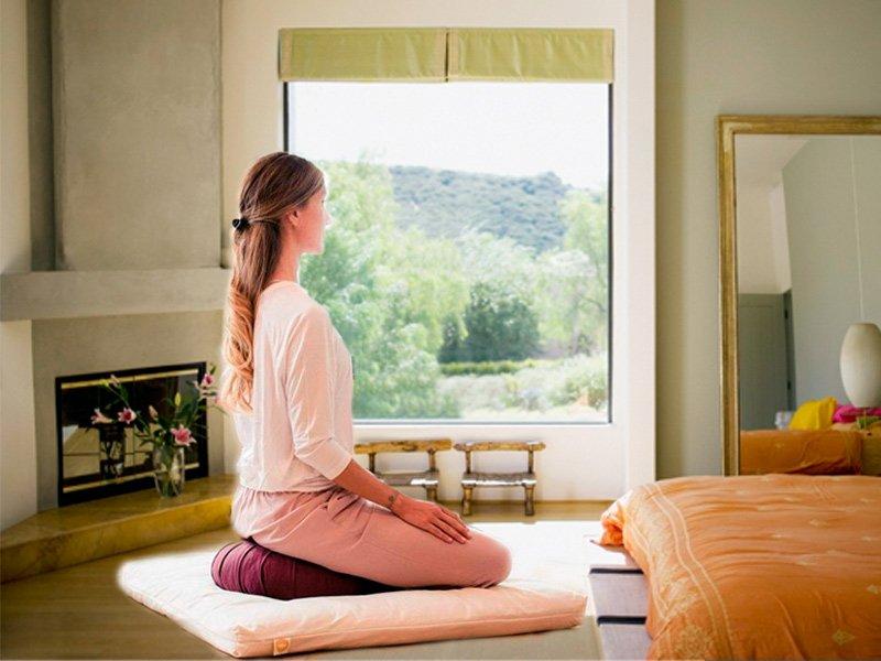 Mujer meditando sobre un zafu